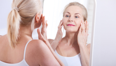 senior woman looking in mirror