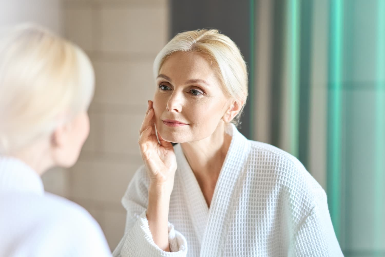 Older woman examining her face in the mirror